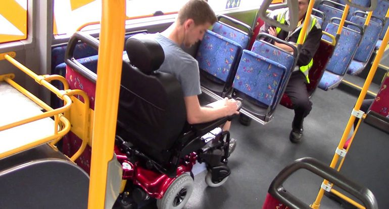 Man in powered wheelchair accessing the bus wheelchair space.